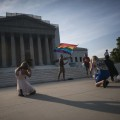 A demonstrator waves a flag while awaiting decisions in two cases regarding same-sex marriage at the U.S. Supreme Court in Washington